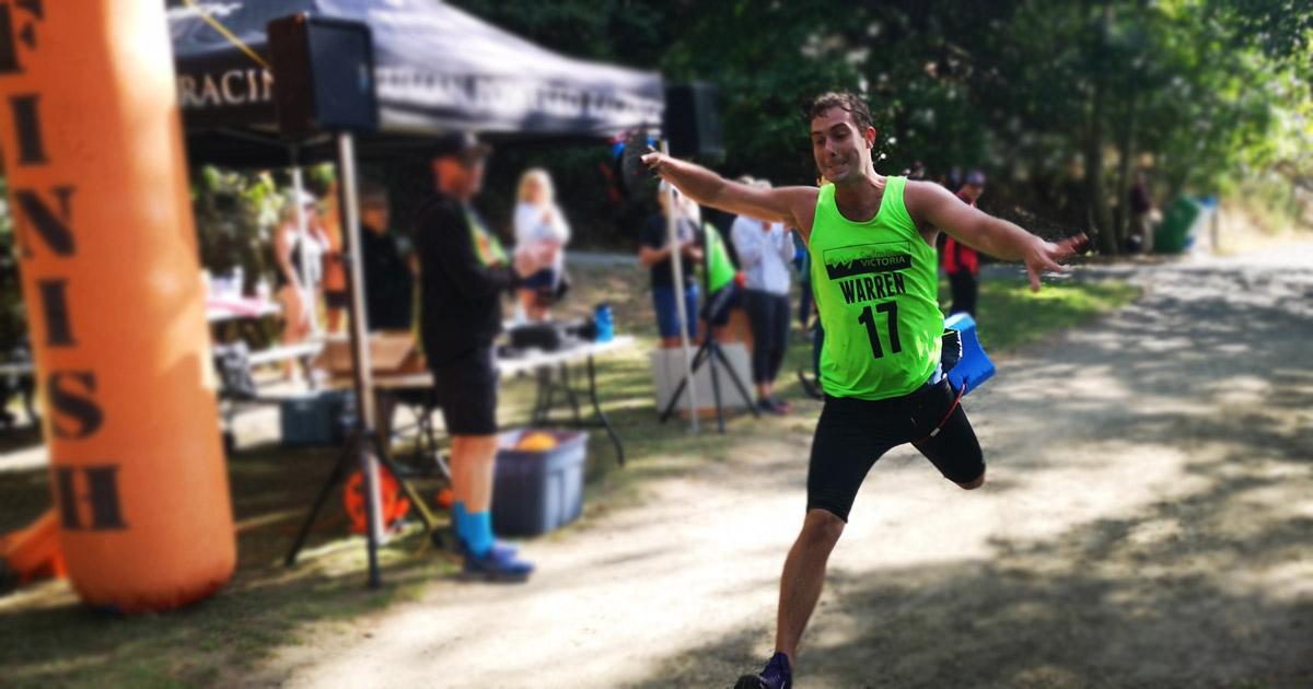 Brandon Warren leaps across the finish line at SwimRunVictoria.