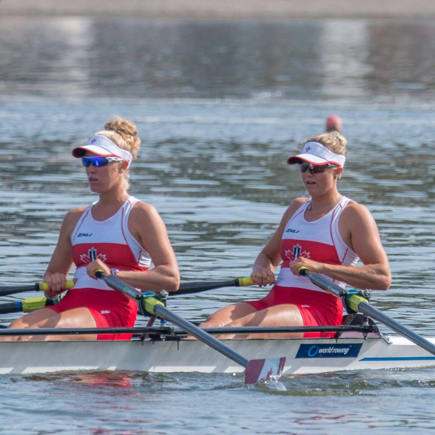 Two women wearing red and white uniforms and visors rigorously rowing on calm water.