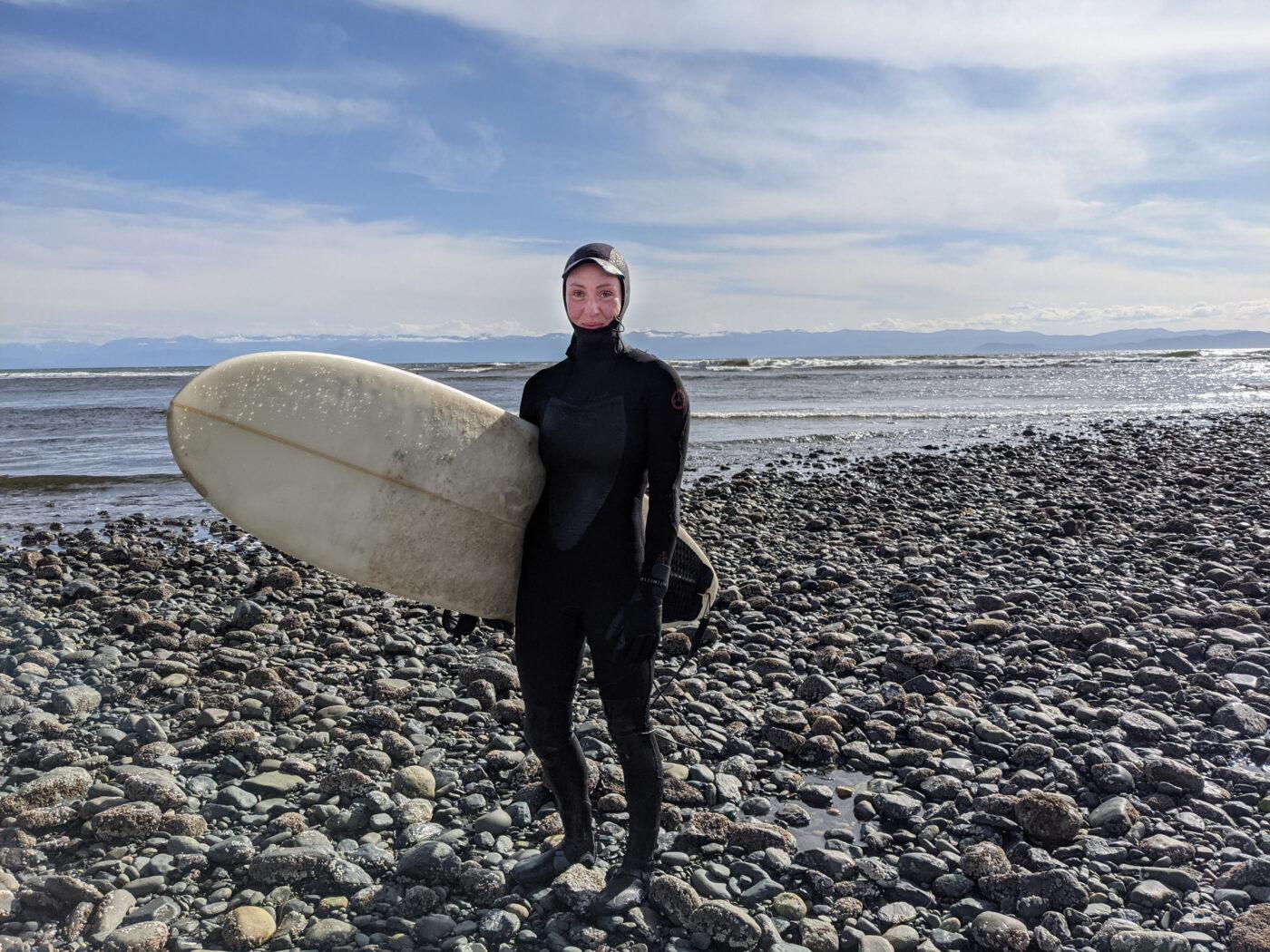 Elana holding her surfboard at Jordan River