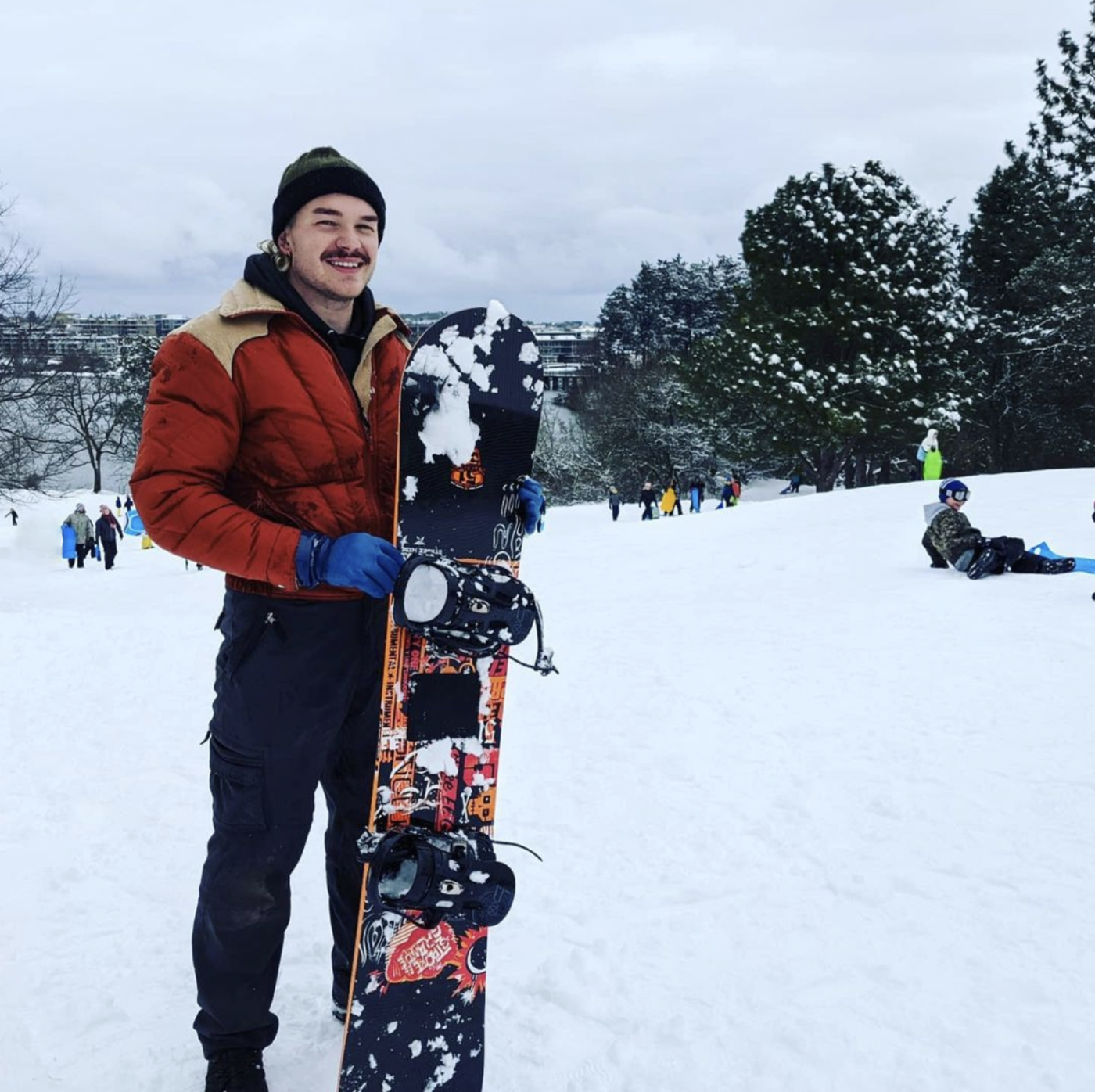 Sascha standing with their snowboard on a snowy hill in Banfield Park