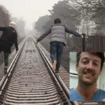An image of 2 people facing away from camera, balancing on the rails of a train track. Overlaid is an image of Andrew Mills smiling and holding up a set of ICS Impulse goggles